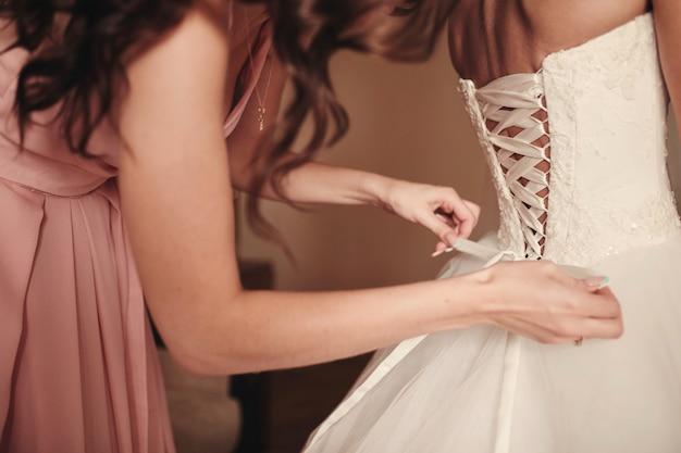 Demoiselle d'honneur aidant mariée à attacher un corset et obtenir sa robe, le matin pour le jour du mariage. Photo Premium