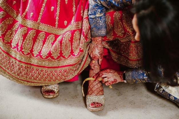 Demoiselle D'honneur Aide à Porter Des Chaussures Mariée Indienne Photo gratuit