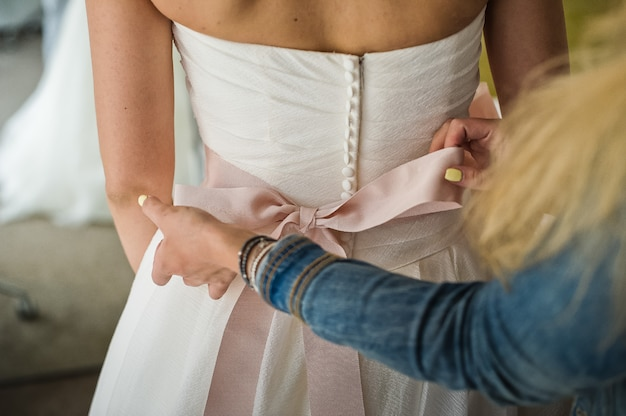 Demoiselle d'honneur aide à porter une robe de mariée Photo Premium