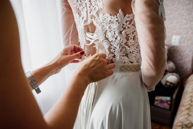 Demoiselle d'honneur attachant des rubans sur la robe blanche de mariage Photo Premium
