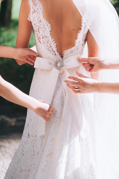 Demoiselle d'honneur boutonnage de la robe sur la mariée, détails de la belle robe de mariée en dentelle Photo Premium