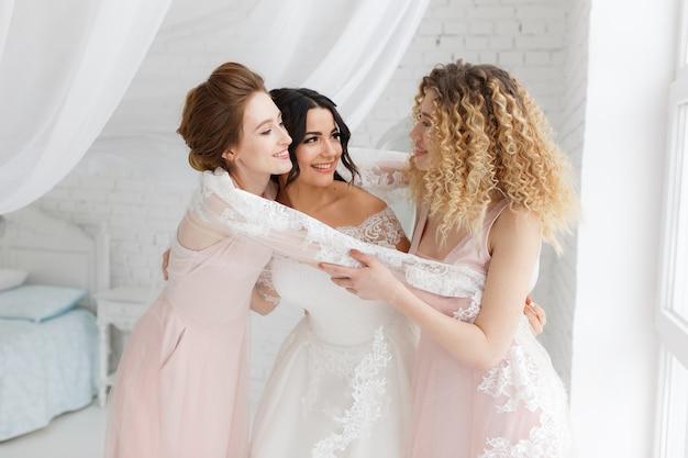 Demoiselle d'honneur étreignant la mariée dans la chambre le matin. Photo gratuit