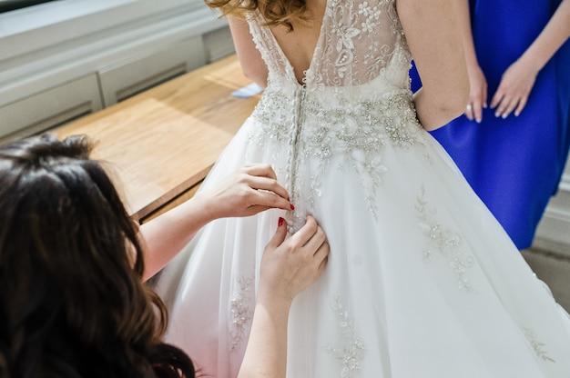 Les demoiselles d'honneur aident la mariée à porter une robe de mariée Photo Premium