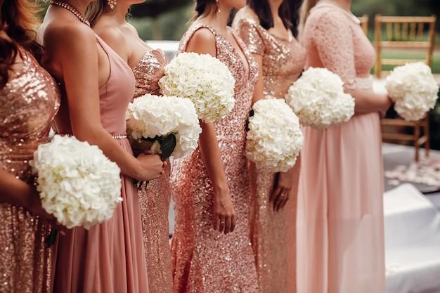Demoiselles d'honneur en robes roses se tiennent avec des bouquets de fleurs blanches dans Photo gratuit