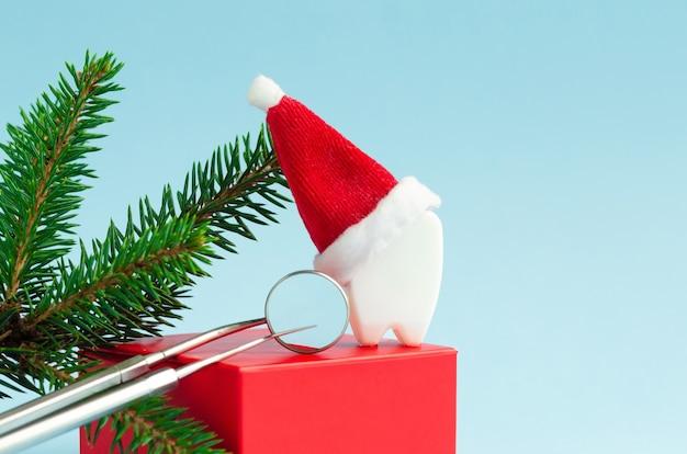 Dent De Jouet En Bonnet De Noel Avec Miroir Et Sonde Pour La Nouvelle Année. Noël Dentaire Créatif Photo Premium