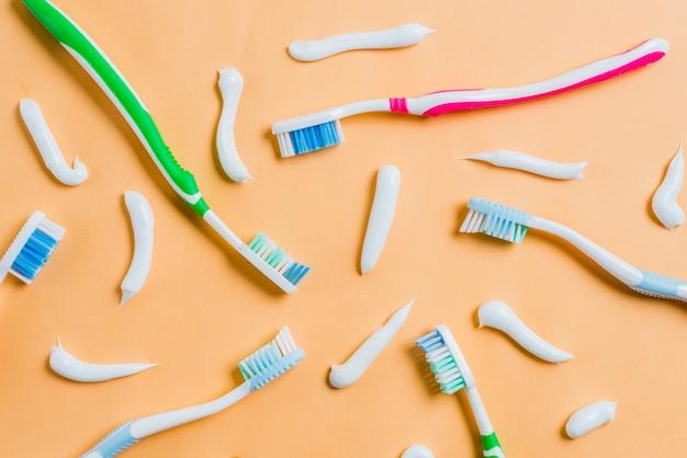 Dentifrice avec différents types de brosses à dents sur fond coloré Photo gratuit