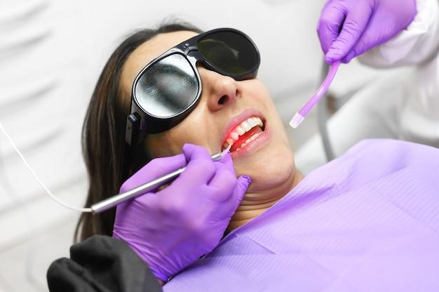 Dentiste à L'aide D'un Laser Dentaire à Diode Moderne. Photo Premium