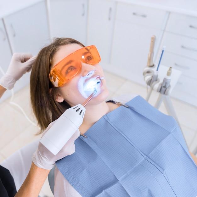 Dentiste examinant les dents du patient avec un équipement de lumière uv dentaire Photo gratuit