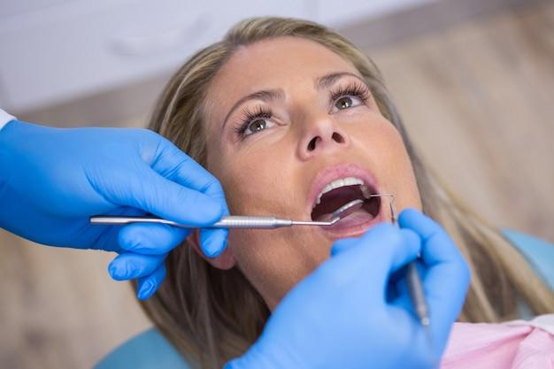 Dentiste Examinant Une Patiente Avec Des Outils Photo Premium