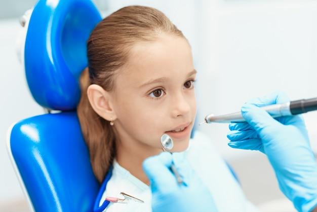 Un dentiste examine les dents d'une fille. soins dentaires. Photo Premium