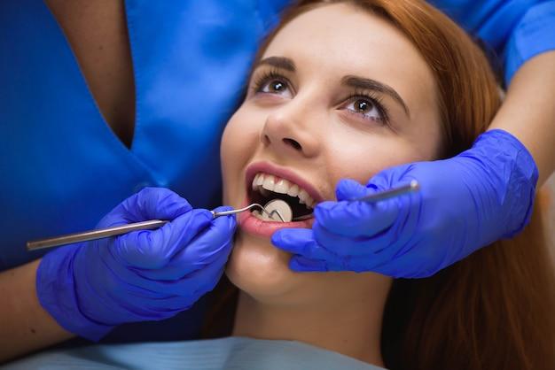 Dentiste examine les dents d'un patient chez le dentiste. Photo Premium