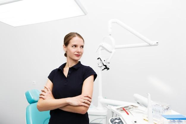 Dentiste Féminine Confiante Se Dresse Au Milieu Du Bureau Blanc Photo gratuit
