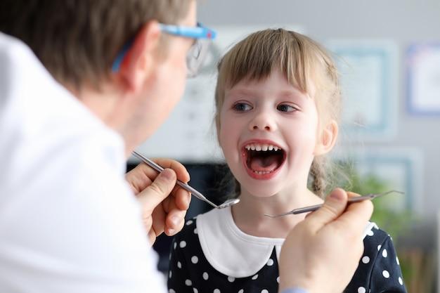Dentiste Mâle Regarder Bouche Ouverte Petite Fille Heureuse Photo Premium