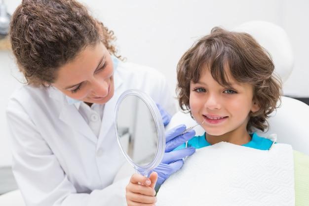 Dentiste pédiatrique montrant le petit garçon ses dents dans le miroir Photo Premium