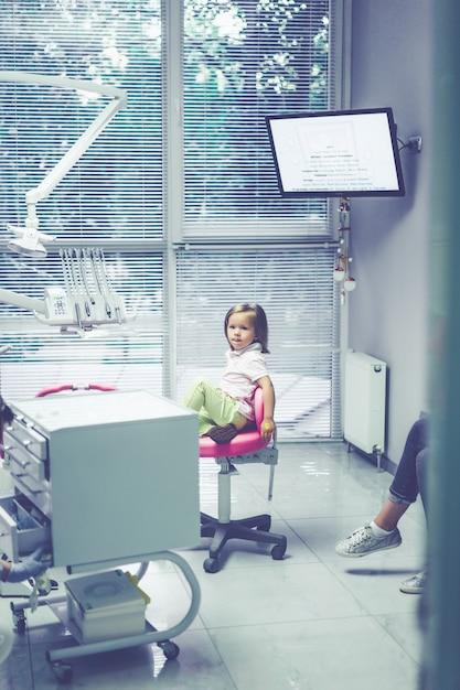 Dentiste pédiatrique. petite fille à la réception chez le dentiste. Photo gratuit