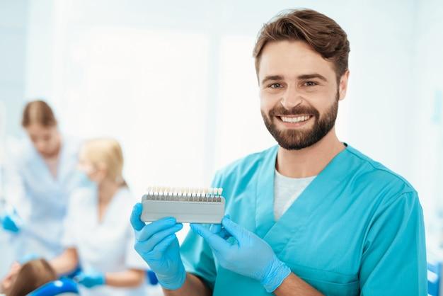 Dentiste posant contre. échelle de couleur docteur dent. Photo Premium