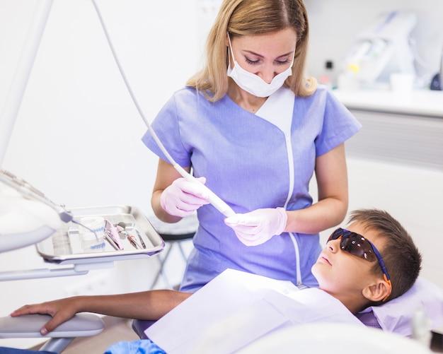 Dentiste utilisant un détartreur à ultrasons pour traiter les dents d'un garçon en clinique Photo gratuit