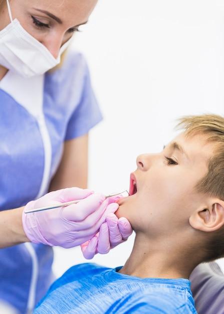 Dentiste vérifiant les dents du garçon avec un détartreur Photo gratuit