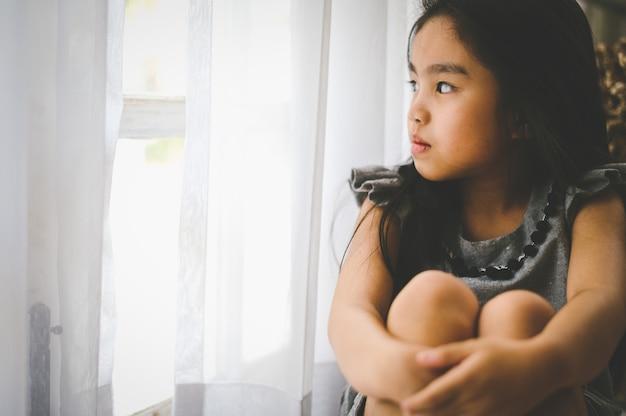 Déprimé petite fille près de la fenêtre à la maison, gros plan Photo Premium