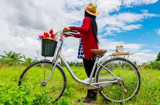 De derrière, une femme porte un chapeau marron et se tient près du vélo vintage Photo Premium