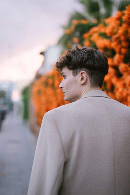 Derrière le jeune homme marchant près des fleurs Photo gratuit