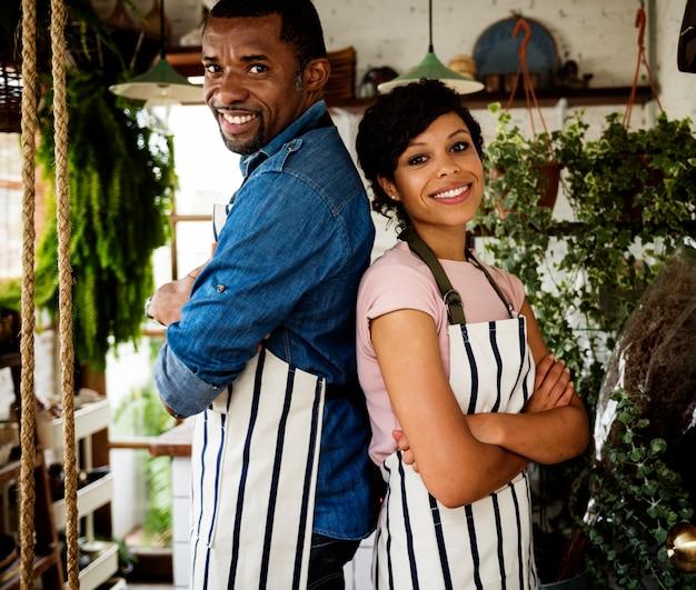 Descendance Africaine Propriétaire Couple Debout à L'intérieur Du Magasin De Fleurs Photo Premium