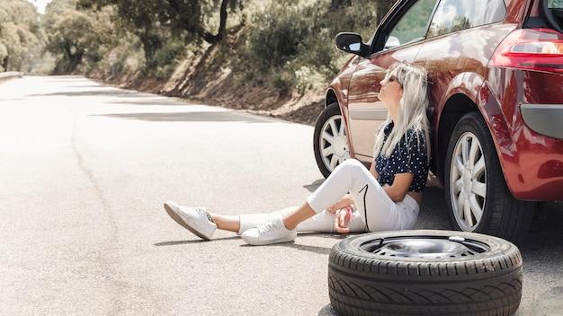 Désespoir femme assise près de la voiture en panne sur la route Photo gratuit