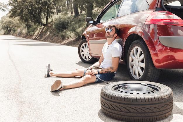 Désespoir homme assis près de la voiture en panne sur la route Photo gratuit