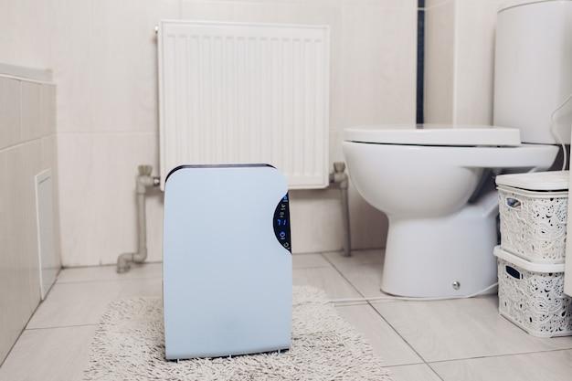Déshumidificateur avec écran tactile, indicateur d'humidité, lampe uv, ioniseur d'air, réservoir d'eau fonctionne dans la salle de bain. sèche-linge Photo Premium