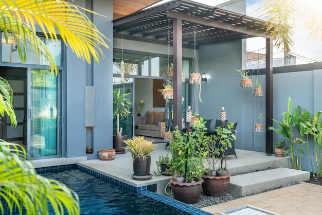 Design extérieur et intérieur montrant une villa avec piscine tropicale avec jardin verdoyant, lit de bronzage et ciel bleu Photo Premium