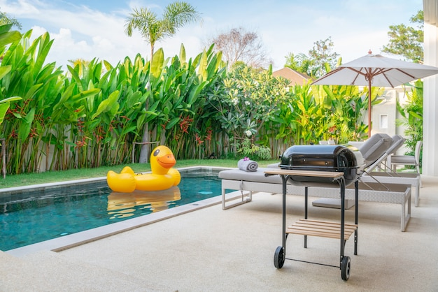 Design extérieur montrant une villa avec piscine tropicale et jardin de verdure Photo Premium