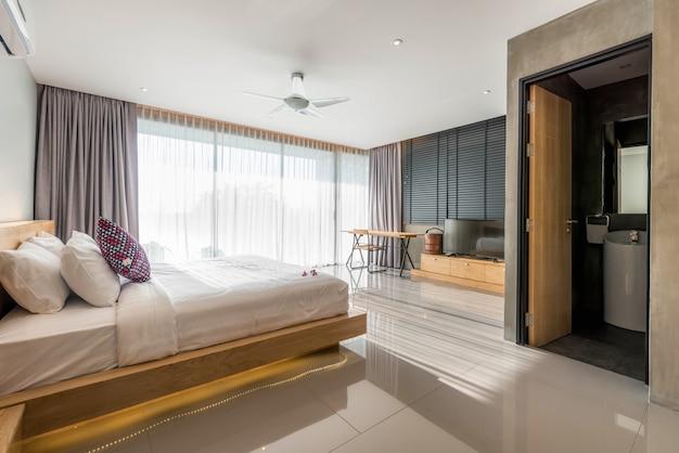 Design d'intérieur dans la chambre à coucher moderne de la villa avec piscine et éclairage Photo Premium