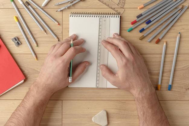 Le designer dessine un croquis dans un cahier sur une table en bois. papeterie. vue d'en-haut. Photo Premium