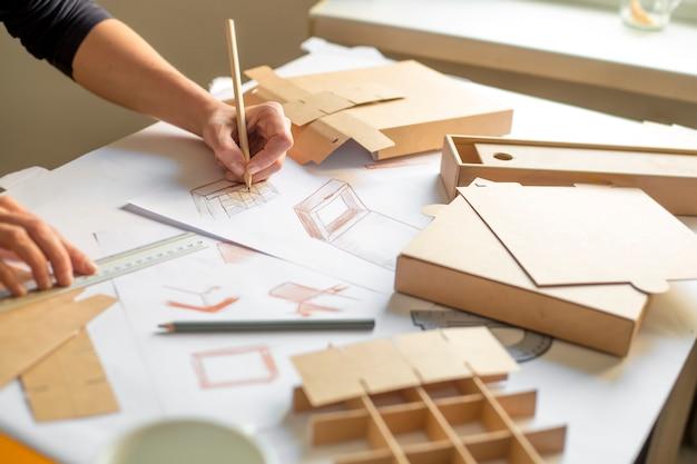 Designer Dessine Une Maquette Pour La Fabrication De Boîtes En Carton. Photo Premium