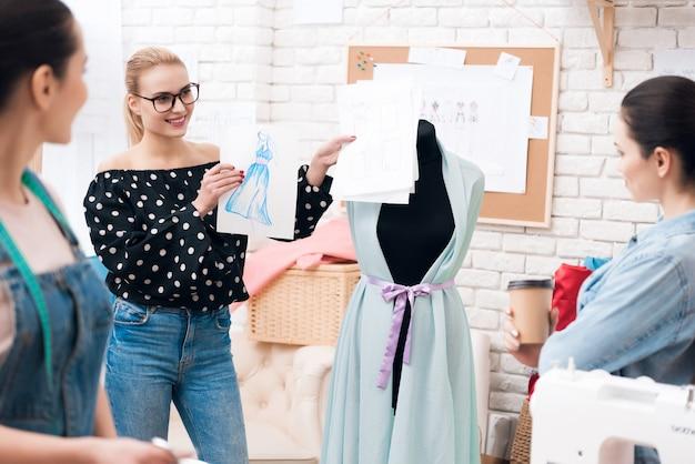 Le designer donne un croquis aux assistants pour s'habiller Photo Premium