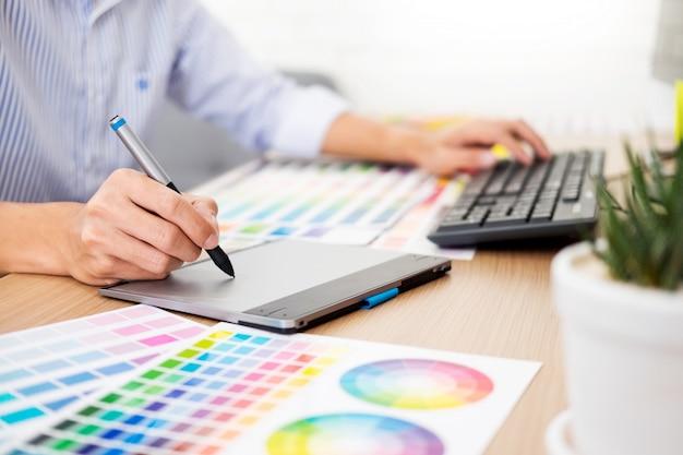 Designer editor at work dessin dessine un nouveau projet sur tablette graphique et palette de couleurs Photo Premium