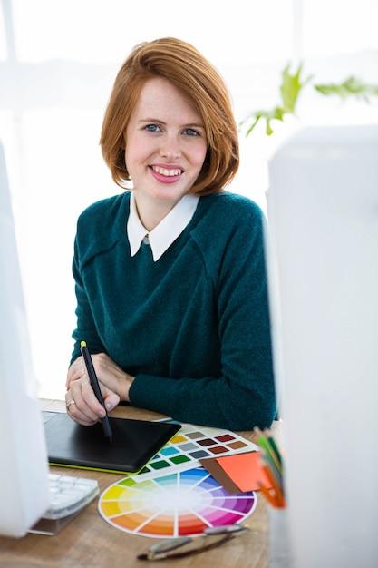 Designer hipster souriant, assis à son bureau, sur une tablette numérique Photo Premium