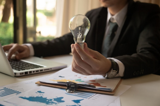 Designer Main Montrant La Stratégie D'entreprise Créative Avec Ampoule Comme Concept Photo Premium