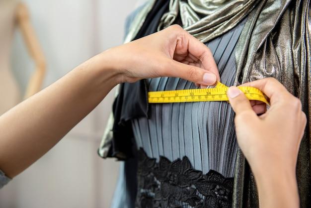 Designer musulman mesurant la taille de la robe avec du ruban à mesurer Photo Premium