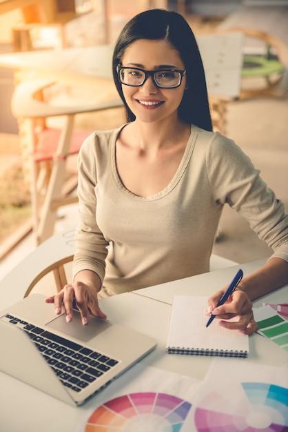 Designer en vêtements décontractés et lunettes utilise un ordinateur portable Photo Premium