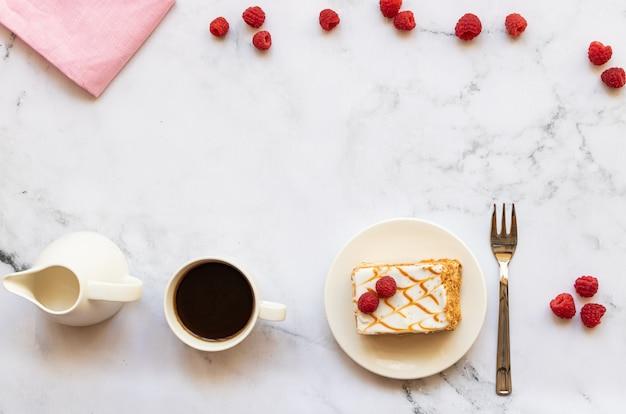 Dessert aux framboises et tasse de café noir sur marbre Photo Premium