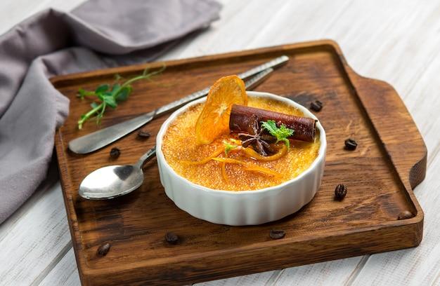 Dessert de crème brûlée à l'orange dans un bol blanc à la cannelle et à la menthe sur fond en bois Photo Premium