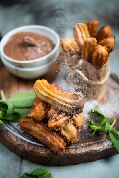 Dessert Espagnol Traditionnel. Churros Au Chocolat Et Au Sucre En Poudre Photo Premium