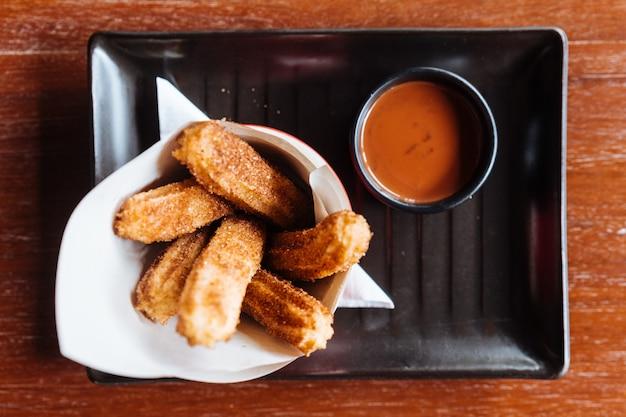 Dessert espagnol traditionnel churros au sucre et à la cannelle. servi avec une sauce au chocolat. Photo Premium