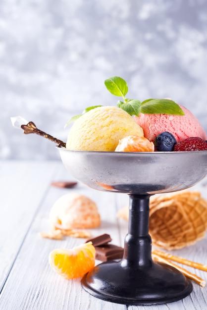Dessert glacé au citron et à la fraise dans un bol en métal avec gaufrette et baies sur bois Photo Premium