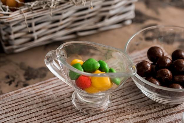 Dessert de pâques délicieux œuf au chocolat avec dragée de couleur bonbon sur table en bois Photo Premium
