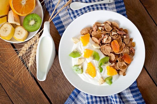 Dessert Sain Avec Muesli Et Fruits Dans Une Assiette Blanche Sur La Table Photo gratuit