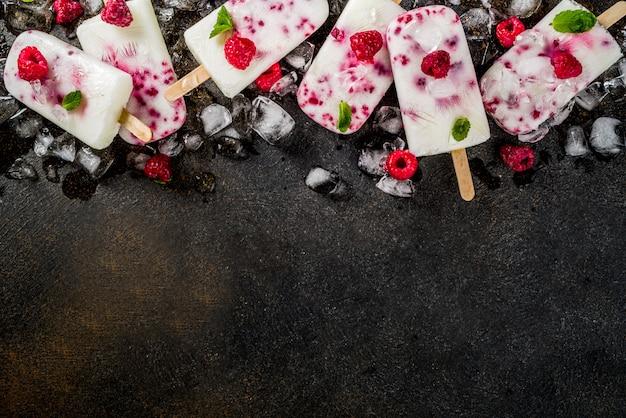 Desserts sucrés de l'été, sucettes glacées bio à la framboise et au yogourt faites maison Photo Premium