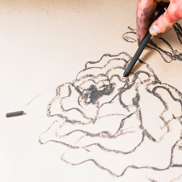 Dessin abstrait avec bâton de charbon de bois à la main Photo gratuit