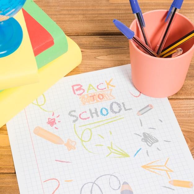 Dessin de couleurs sur papier à l'école sur une table en bois avec des livres et des crayons Photo gratuit